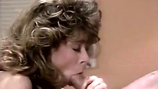 Busty bombshell Christy Canyon gives hot blowjob to her co-worker
