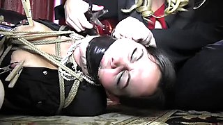 Slave girl in a skirt and blouse tied up by mistress
