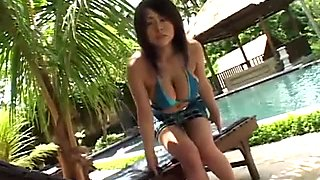 Awesome busty and sexy Asian chick poses in bikini near the pool