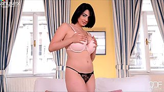 Sensual brunette juggles her massive impressive boobies on a camera
